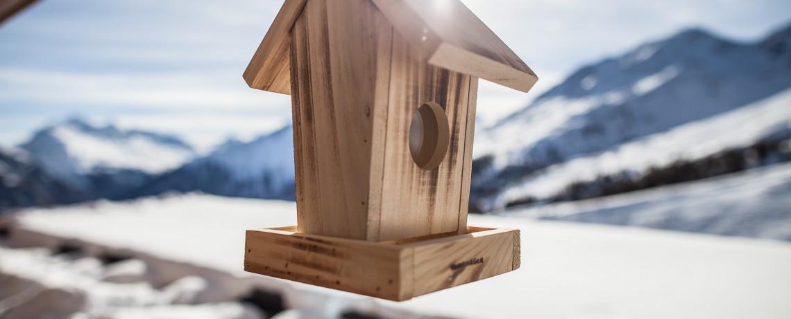 kleines Vogelhäuschen hängt am Balkon